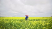 безмятежность : Slow motion of girl and boy running towards each other in the meadow and hugging passionately