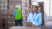 Close up of woman in helmet browsing digital tab while laborer rearranging boxes with merchandise in the background