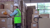 shipping : Close up of worker uncarting load and arranging boxes in piles
