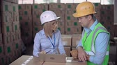 shipping : Dolly in of supervisor giving verbal reprimand to the laborer in warehouse