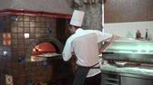Tracking shot of young pizzaiolo putting pizza in oven Wideo