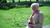 зелень : Old thoughtful lady sitting outdoors with laptop on a sunny day Стоковые видеозаписи