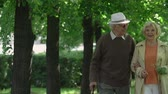 безмятежность : Elderly couple in love approaching camera walking in the park Стоковые видеозаписи