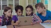 grade : Four kids having fun with digital tablet Stock Footage
