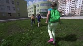 setembro : Camera following three kids with backpacks hurrying at school running on the lawn in slow motion