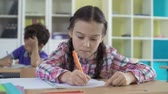 grade : Close up of girl focused on drawing, her classmate in the background