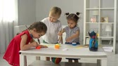 jardim de infância : Three toddlers drawing with paint on one huge canvas Stock Footage