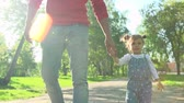 bem aventurança : Tracking slow-motion of unidentified father walking with his baby in the park, holding her hand