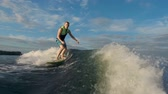 jumping : Man in life vest approaching camera riding surfboard