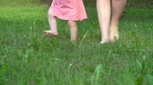 começo : Low angle of woman walking with child barefoot on grass Vídeos