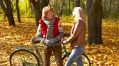 novembro : Girl and boy flirting in autumnal park standing at the bicycle
