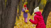 novembro : Twin sisters going towards each other with bunches of maple leaves Stock Footage