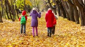 novembro : Four children moving off from the camera enjoying autumnal walk in the park