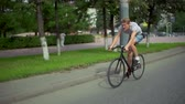 fixní : Tracking shot of man riding fixed gear bicycle passing by buildings of the city in slow motion