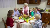 aplauso : Family of three generations gathered for festive meal, grandmother putting roasted turkey on the table and everybody applauding