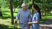 doença : Close up of caring nurse explaining to senior patient how to use walker