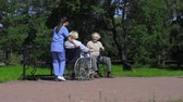doença : Uniformed nurse driving wheelchair with senior woman to bench where old man with stick is sitting