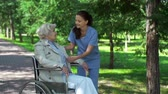 doença : Close up of pretty nurse attending to mature patient in wheel-chair