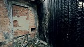 assustador : Shaky camera moving along the abandoned burnt down house, destroyed wall cut by bloody saw Stock Footage