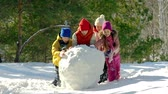 śnieżka : Four kids busy making snowman  Wideo