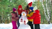 únor : Five kids finishing their snowman happy with the result