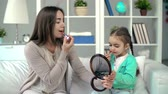 but : Mother showing daughter lipstick applying technique, girl failing to rouge correctly but having lots of fun