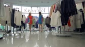 cabide : Two shoppers walking with bags full of purchases out of the boutique Stock Footage