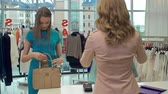 caixa : Sales Assistant standing with her back to the camera packing purchase, customer handing plastic card to her