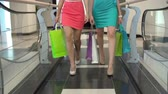 consumismo : Low section of two shoppers strolling along the shopping center in slow motion
