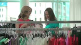 conselho : Close up of two girlfriends discussing clothes in apparel department