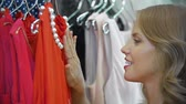 cabide : Close up of stunning lady looking at red dress in the shop, examining it carefully and taking it to fitting room