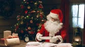 wróżka : Close up of Santa Claus skimming letters, looking at table clock and clutching his head