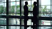 management : Silhouettes of two businessmen greeting each other with a handshake