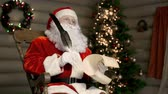 wish : Santa sitting in rocking chair with bothered face after reading a letter