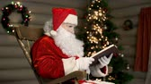 página : Santa Claus reading to himself in a rocking chair