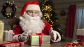 магия : Close up of Santa Claus packing gifts in beautiful boxes with care