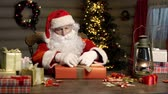 магия : Man in Santa Clause costume decorating gift packages