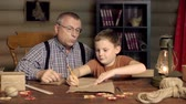 aprendizagem : Close up of grandpa teaching his grandson to draft with a ruler