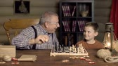 checkmate : Grandpa happy to capture chess pawn of his grandchild, shocked by his counterstrike