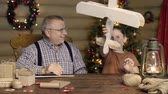 vnuk : Boy playing with plane dummy created by himself with assistance of his granddad