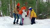 únor : Group of kids making a snowman together