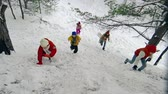 scrambling : Right from above view of five jolly children climbing up the snowy hill