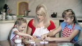 mamãe : Mother teaching daughters to shape dough with cookie cutters