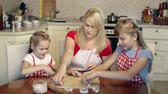 ramekin : Mother and daughters shaping cookies with cookie cutters