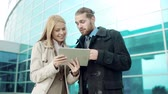 intelligent : Low angle of business partners browsing internet on touchscreen device standing in the street Stock Footage