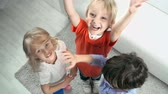 três pessoas : Direct from above shot of three kids showing unity with gesture and waving hands looking at camera Vídeos