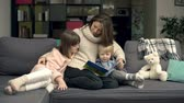 delicadeza : Family of three cuddling on couch and reading