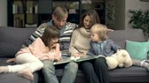 dearest : Family of four cuddling on sofa in living room and watching photo book