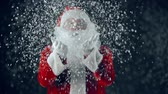 snowfall : Man in Santa Claus costume catching snowflakes in hands and blowing them at camera