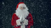 легенда : Close up of Santa Claus against black background clapping hands in the snow